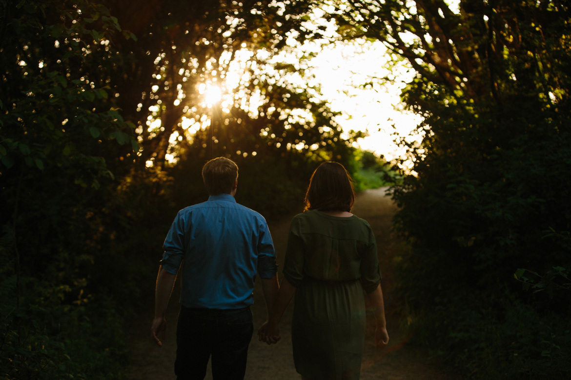Couple walking in forest during sunset engagement photos at Discovery Park in Seattle, WA