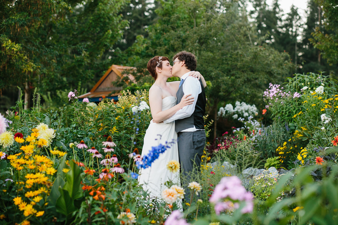 Bride and groom kissing in flowers during sunset at Fireseed Catering wedding on Whidbey Island, WA