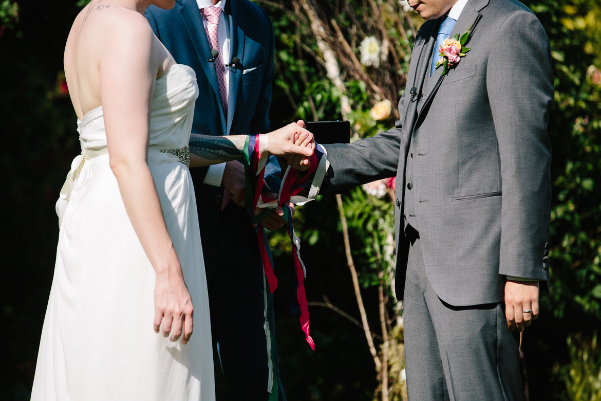 Officient tying ribbons during wedding ceremony at Fireseed Catering on Whidbey Island