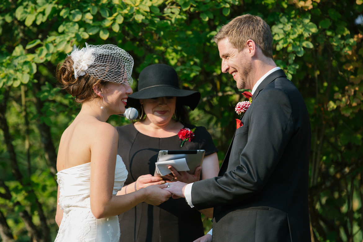 Bride and groom exchanging rings during wedding ceremony at Center for Urban Horticulture in Seattle, WA