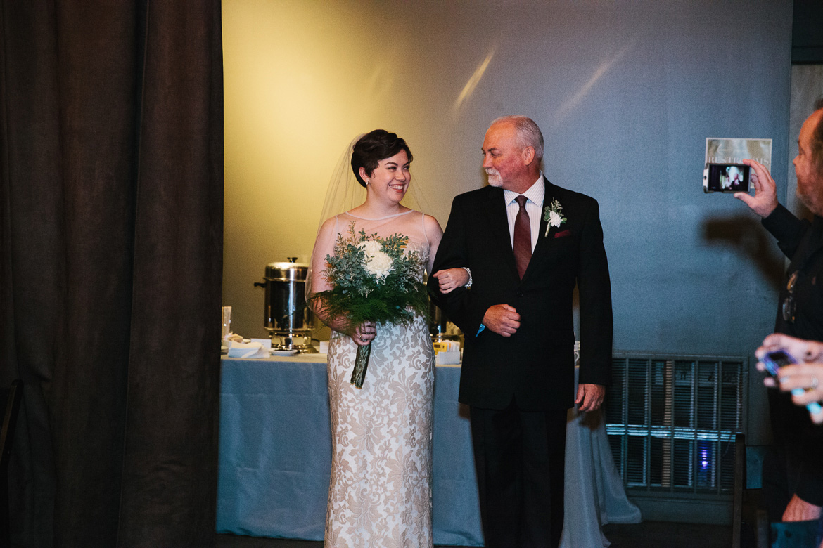 Bride walking down aisle with her father during wedding ceremony at Melrose Market Studios in Seattle, WA